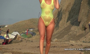 Transparent swimsuit and stripped on the beach